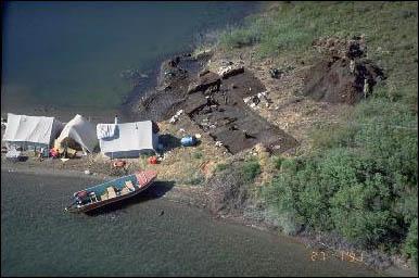 Vue aérienne d'un site d'excavation archéologique sur le bord de l'eau.