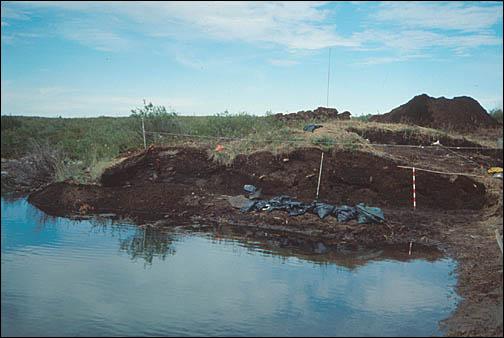 Une butte de terre sur le site de fouille archéologique au bord de l'eau.