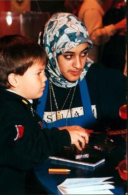 Une jeune femme voilée aidant un enfant.