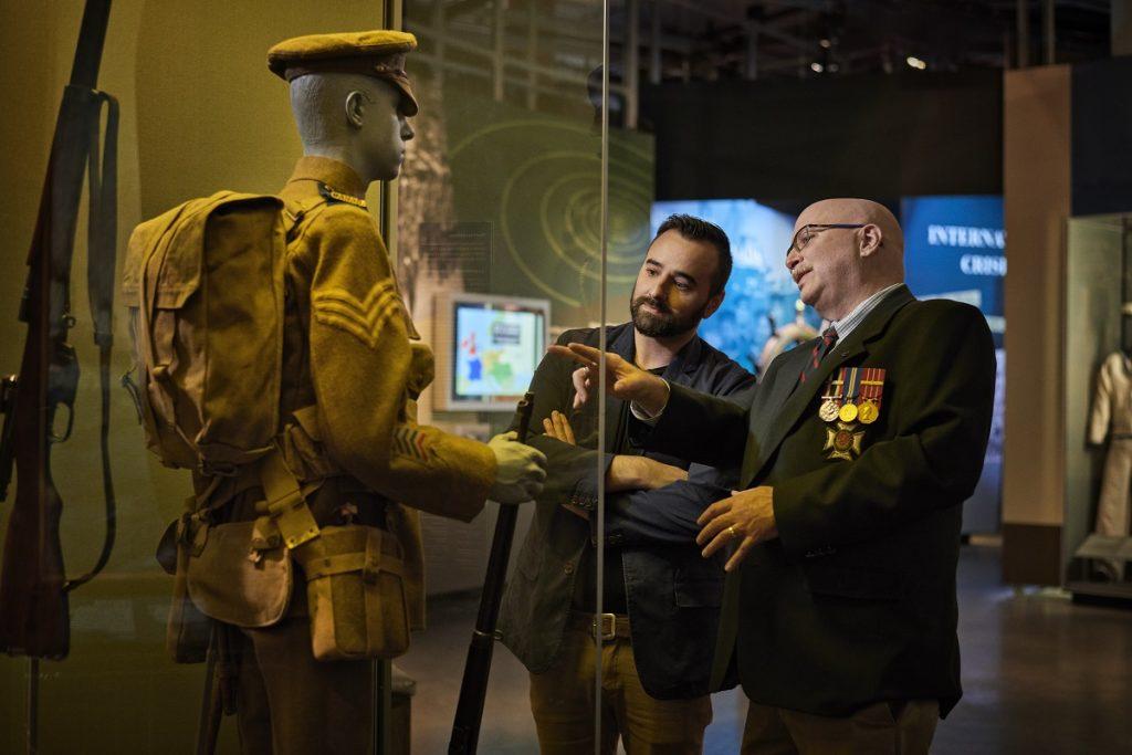 Visiteurs examinant un uniforme exposé dans la Gallerie du Musée canadien de la guerre