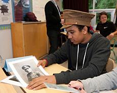 Un élève de l'école secondaire Brookfield examine le contenu d'une boîte de découverte de la Première Guerre mondiale, fourni par le programme Ligne de ravitaillement.