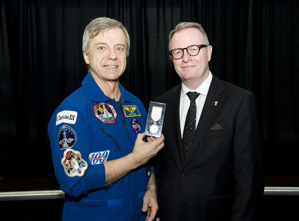 De passage au Musée canadien de l'histoire le 15 décembre 2014, l'astronaute canadien Robert Thirsk, Ph. D., en a profité pour revoir la médaille qu'il avait apportée à bord de la Station spatiale internationale en 2009. Musée canadien de l'histoire, IMG2014-0237-0016-Dm