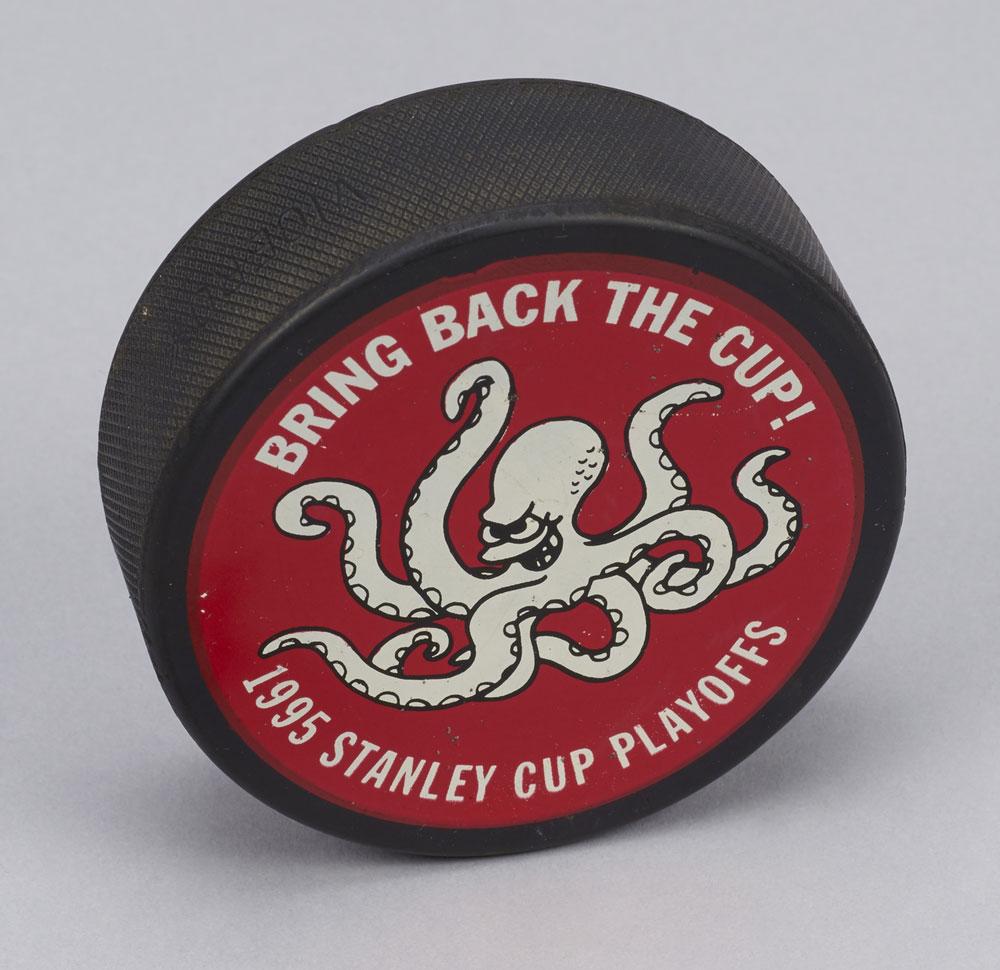 John Finley, l'ancien médecin de l'équipe des Red Wings de Détroit, a conservé cette rondelle de hockey des séries éliminatoires de 1995. L'équipe n'a pas remporté la Coupe Stanley cette année-là, ayant perdu contre les Devils du New Jersey lors de la série finale. Photo : Musée canadien de l'histoire.
