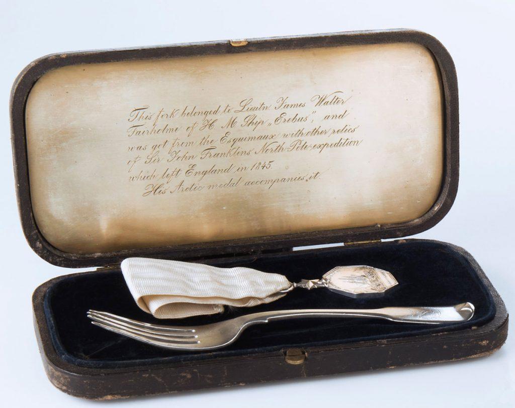 Fourchette à dessert et médaille de l'Arctique conservées dans un petit boîtier. Musée canadien de l'histoire, collection Lieutenant Fairholme, 2015.46.1.1; 2015.46.1.2 a-b; 2015.46.1.3, IMG2016-0321-0015