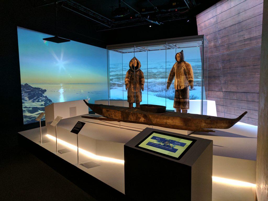 Un kayak et des tenues d'été inuits, datant tous de plus de 100 ans, au National Maritime Museum. La station d'écoute (en bas à droite) permet d'écouter Louie Kamookak expliquer l'importance constante de la tradition orale inuite. Photo Musée canadien de l'histoire