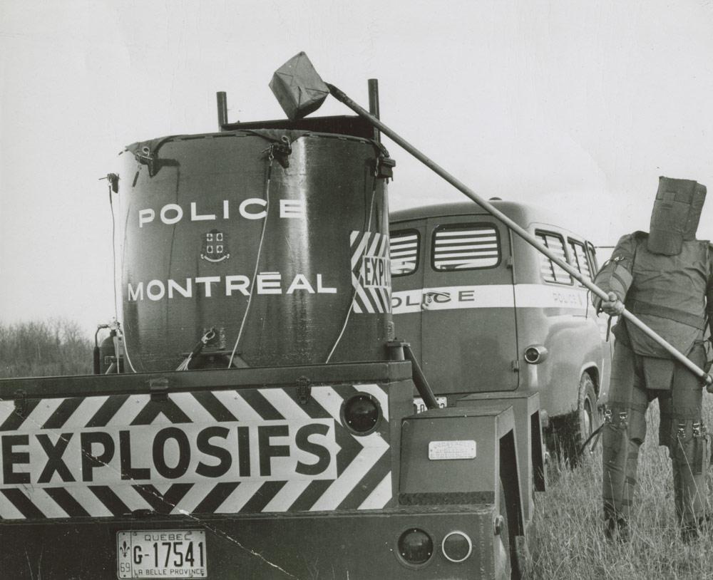 Le sergent Robert Côté, à droite de la remorque anti-bombes de la police de Montréal, en 1968. Musée canadien de l'histoire, Archives photographiques, IMG2016-0278-0001-Dm, photographe inconnu.