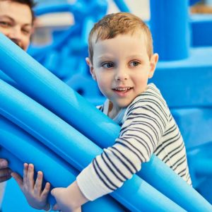 Enfant avec des morceaux de mousses bleus