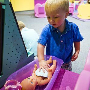 Un petit garçon baigne sa poupée