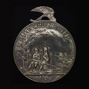 Médaille circulaire représentant deux personnages assis côte à côte, avec les mots «Happy while united» («Heureux et unis») et l'année 1764.