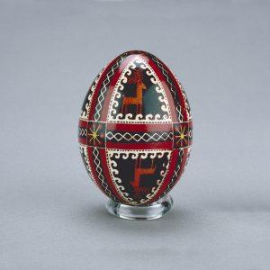Un œuf de Pâques ukrainien décoré d'images en miroir de chevreuils, divisées par des formes de spirales et de rubans entrecoupées de fleurs.