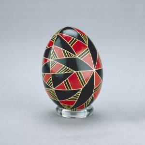 Un œuf de Pâques ukrainien décoré de formes de diamants contrastés noires et rouges, séparées par des lignes jaunes.