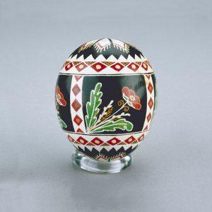 Un œuf de Pâques ukrainien décoré de formes de diamants et de triangles rouges, blanches, noires et jaunes, ainsi que des motifs de coquelicot.