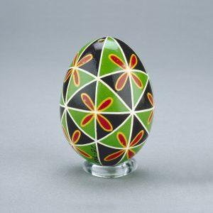 Un œuf de Pâques ukrainien décoré d'un motif de triangles noirs et verts entrecoupés de vives fleurs rouges et jaunes.
